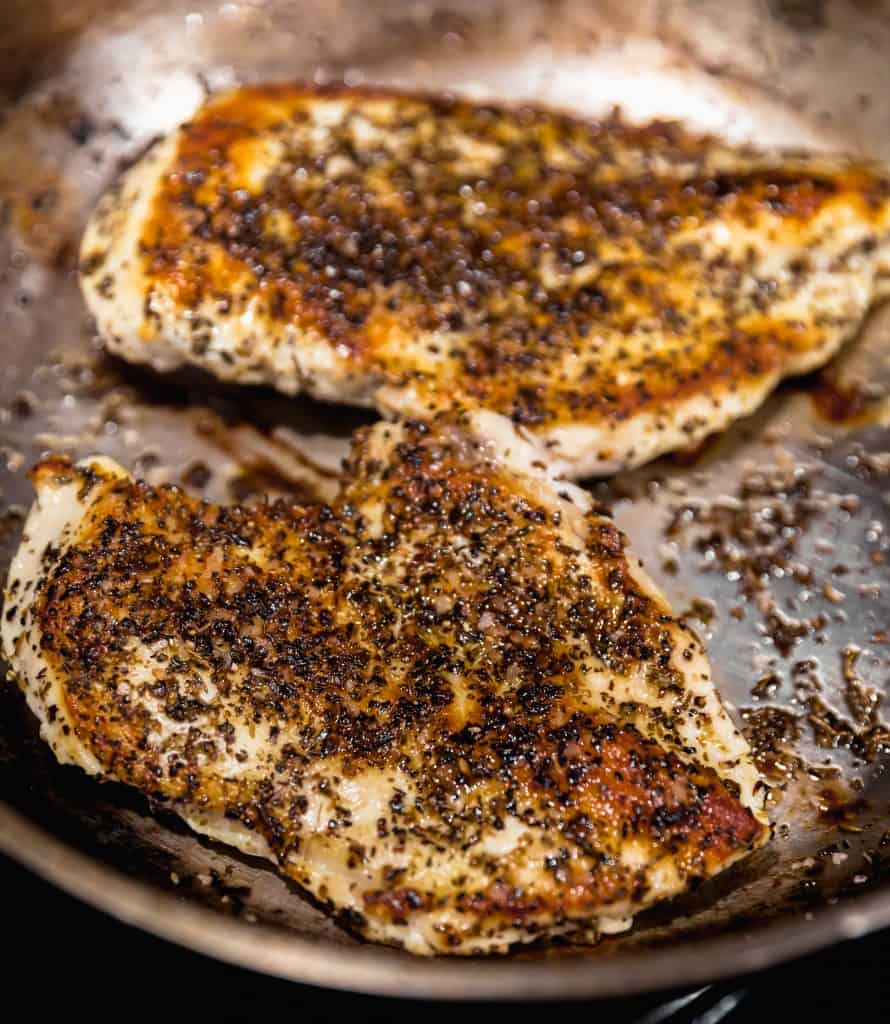 2 chicken breasts with oregano, salt, pepper and dried basil seared to a dark golden brown in a medium sized skillet