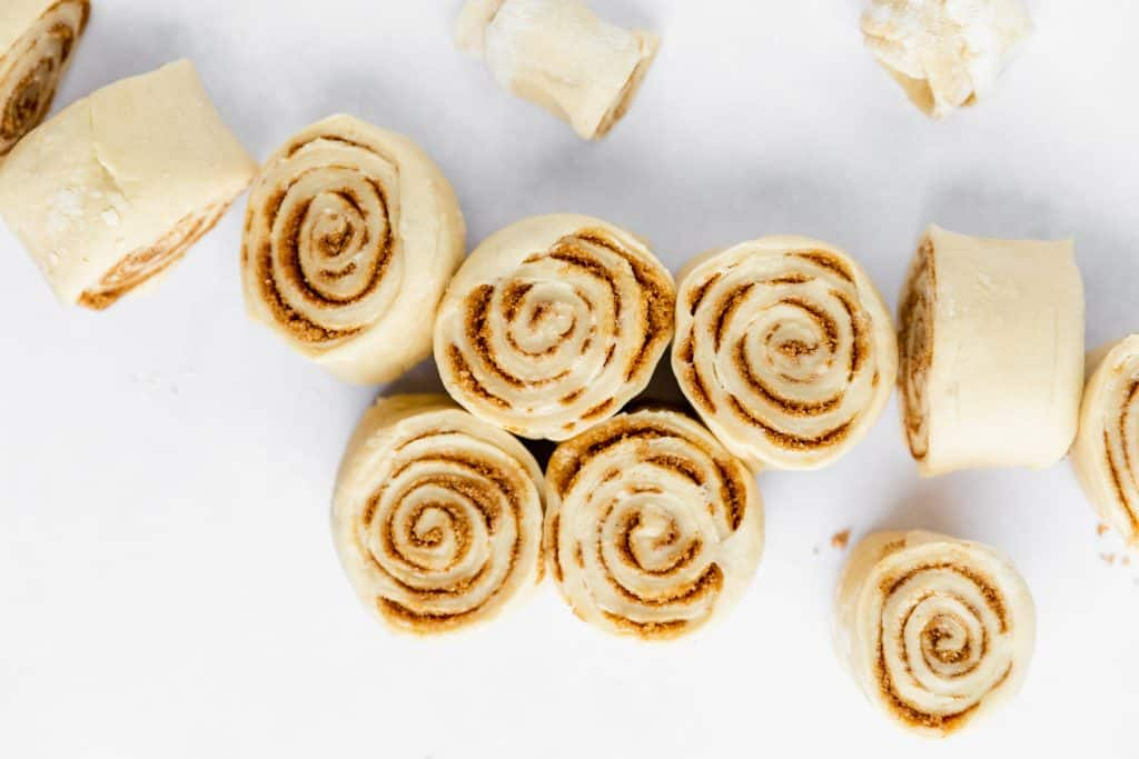 raw cinnamon roll dough rolled up and cut into 1.25 inch rolls before the second proofing