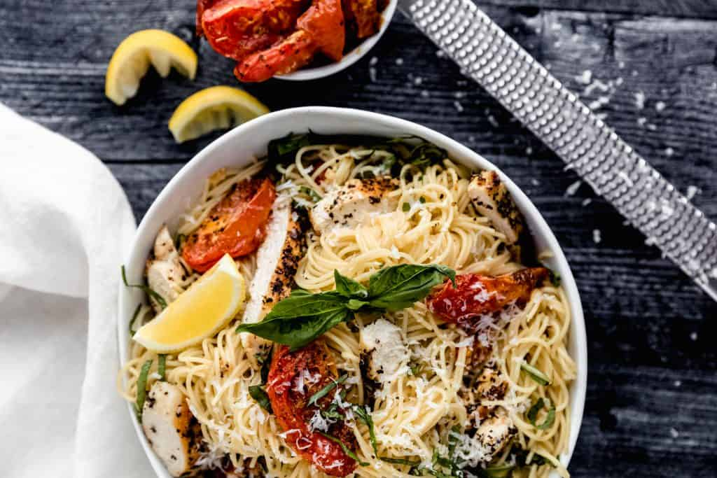 bowl of garlic chicken pasta sprinkled with asiago cheese, roasted tomatoes, fresh basil and a lemon wedge on top of a dark wood surface with a microplane zester and 2 squeezed lemon wedges and a bowl of roasted tomatoes