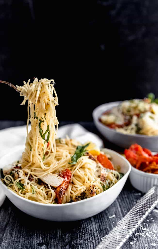a white bowl with garlic chicken pasta inside, roasted tomatoes, fresh basil and a lemon wedge. The angel hair pasta is twisted up on a fork and lifted in the air over the top of the pasta bowl
