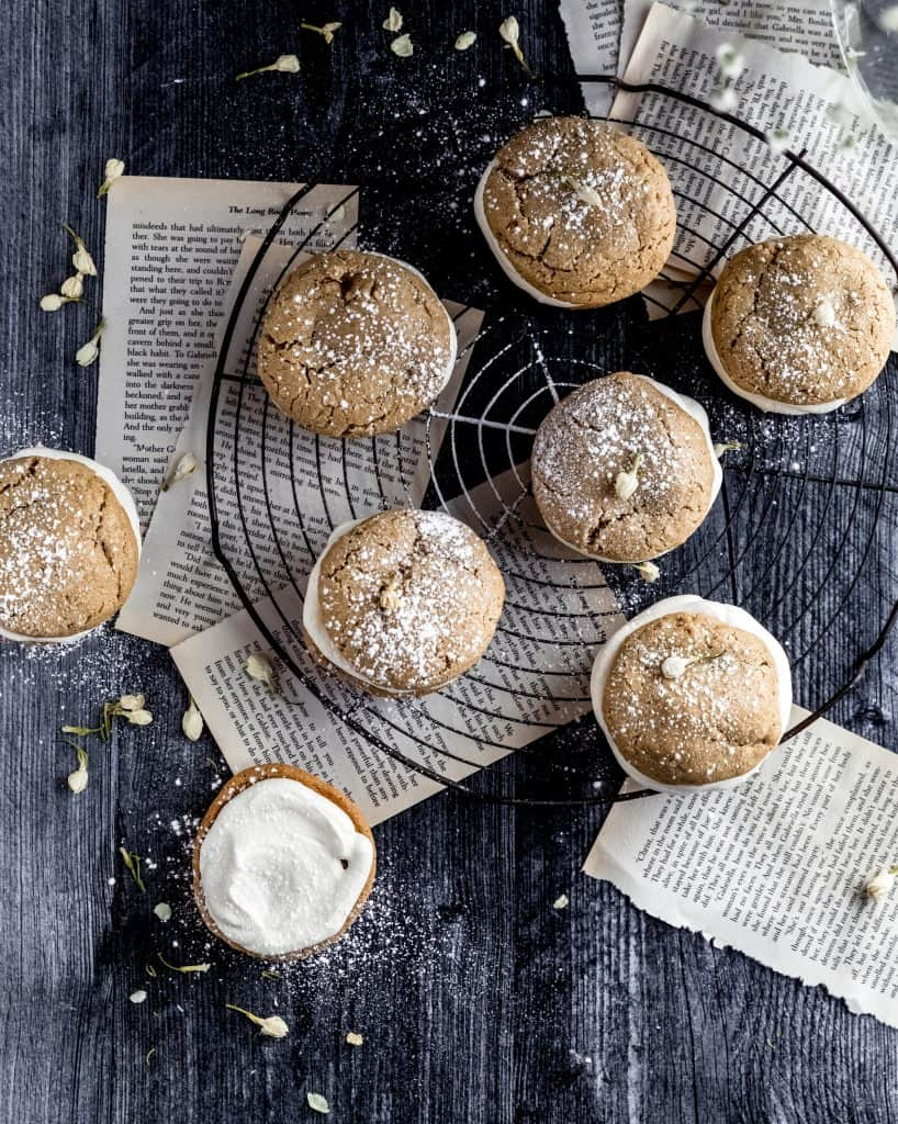 oatmeal cream pies on top of a circular cooling rack with book pages underneath dusted with powdered sugar and dried white flowers. one oatmeal cream pie is off to the side, open face so you can see all the cream