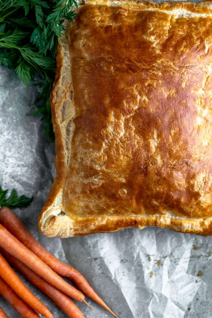 puff pastry baked to medium golden brown on top of parchment paper with carrots with green tops next to it