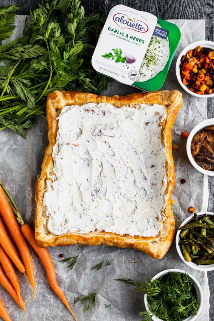 puff pastry with garlic and herb cheese spread over the top and small bowls of asparagus, carrots and shallots to the side