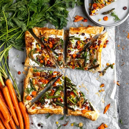Asparagus tart with roasted veggies and carrots with green tops laying to the side. one triangle of tart missing out of the square