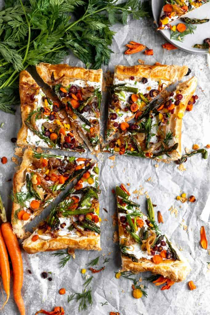 asparagus tart cut into triangles with a piece missing and one pulled down to the side. topped with veggies and fresh herbs