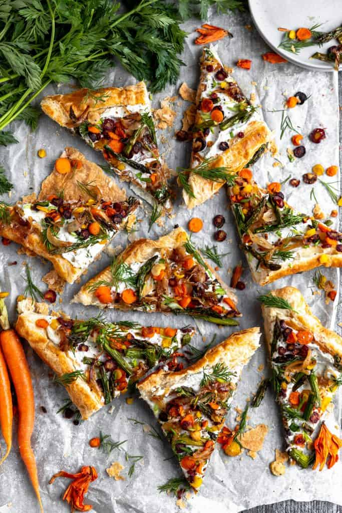 triangles of asparagus tart with fresh herbs on top spread out facing all different ways