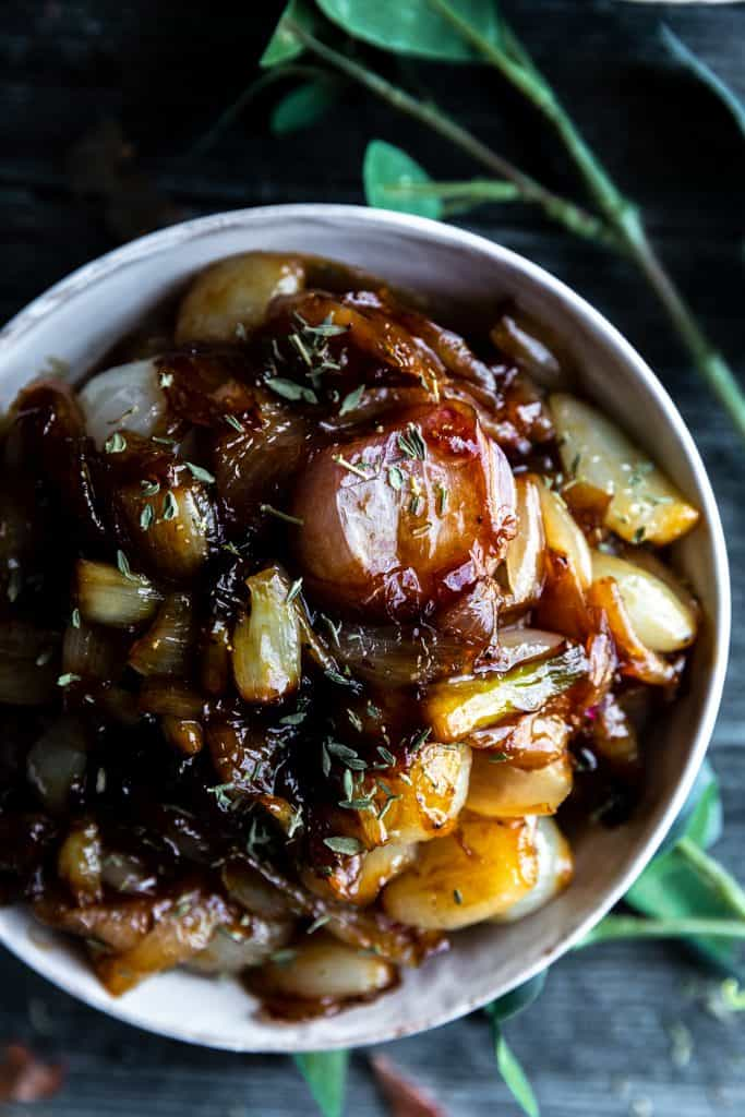 a bowl of glazed shallots sitting on top of a dark surface