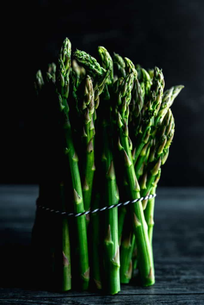 a bundle of asparagus up against a black background tied together with black and white twine