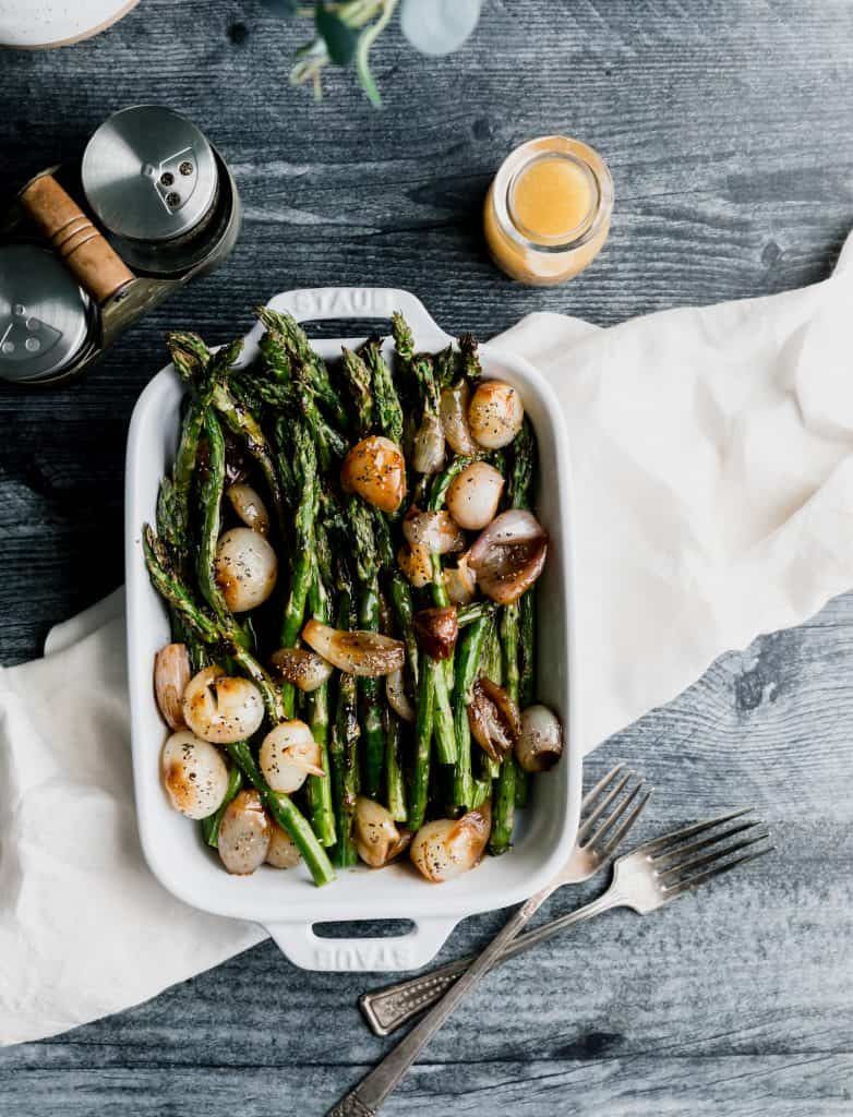 overhead shot of asparagus in a white baking dish with glazed shallots and sherry vinaigrette on top. sitting on top of a light colored linen on a dark weathered wood surface with salt and pepper shakers in the top left corner