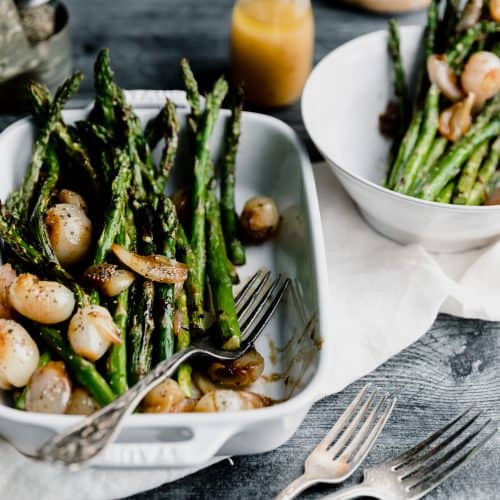 grilled asparagus sitting in a white baking dish topped with glazed shallots and sherry vinaigrette with one fork in the dish and 2 forks on the side. another plate of asparagus in the top right corner with the dressing to the left if it