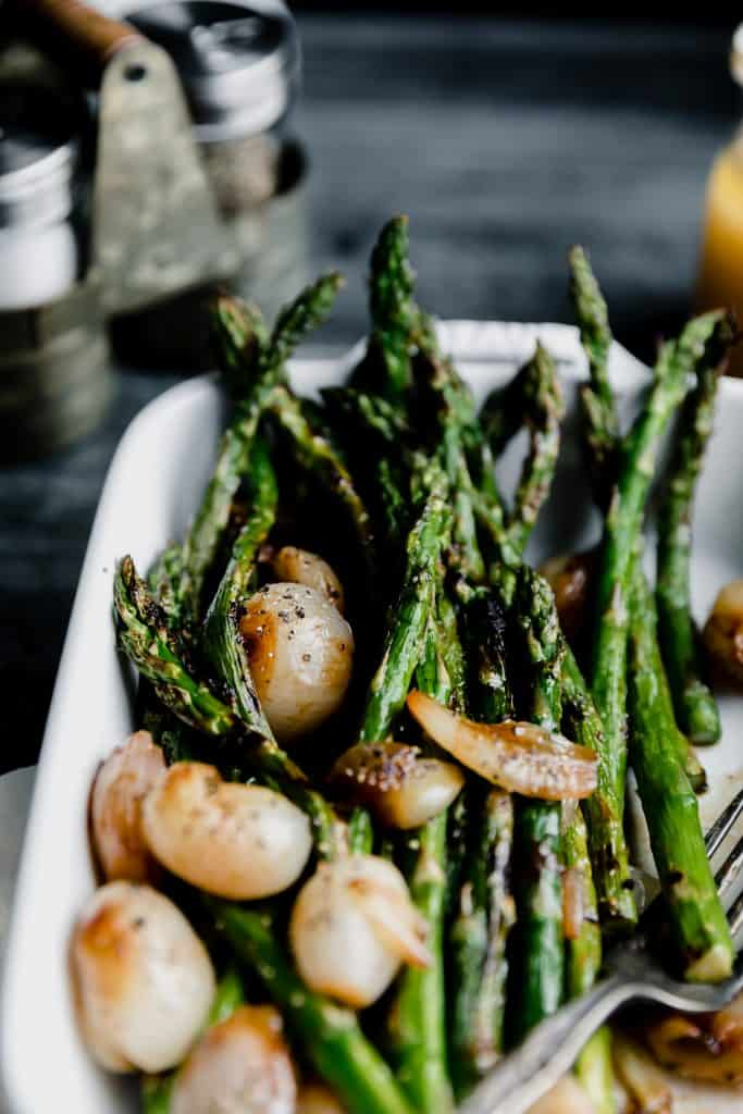 asparagus and shallots in a white baking dish with a metal salt and pepper holder in the back