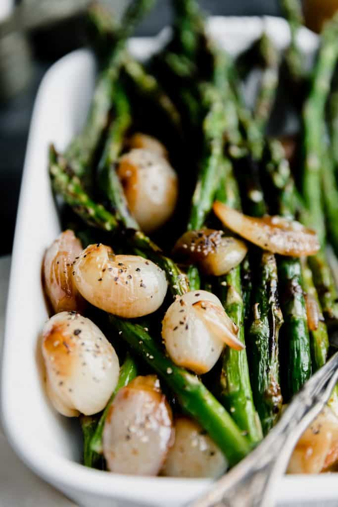 close up of grilled asparagus in a white baking dish with glazed shallots and sherry vinaigrette with a fork in the corner of the pan