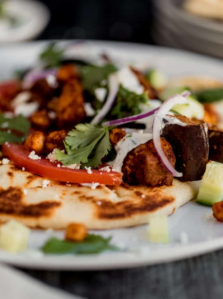 close up of eggplant shawarma on a white plate with cilantro, tomato and red onions