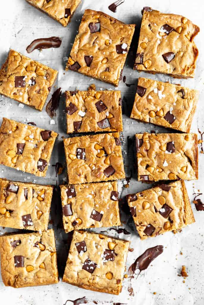the best blondies with chocolate, butterscotch and toasted pecans spread out in rows on a white surface