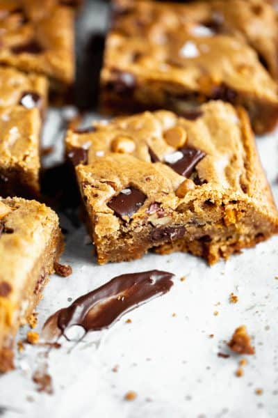 the best blondies with chocolate, butterscotch, toasted pecans and sea salt sitting on a white surface with a smear of melted chocolate in front of on of the pieces
