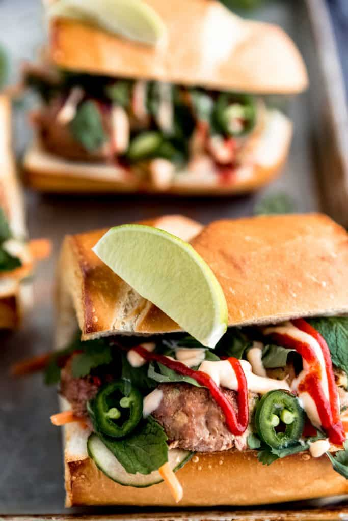 close up of the meatball banh mi with sriracha sauce, sweet chili sauce, lime wedge and various green herbs