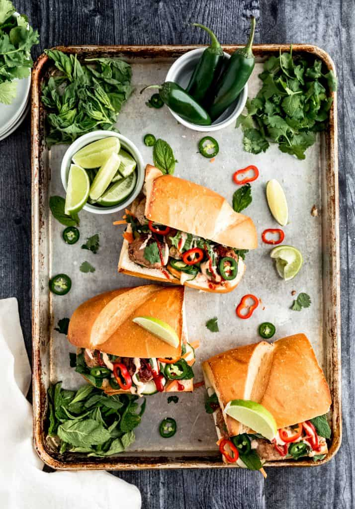 a pan of meatball banh mi with herbs, jalapenos and lime wedges scattered throughout the tray