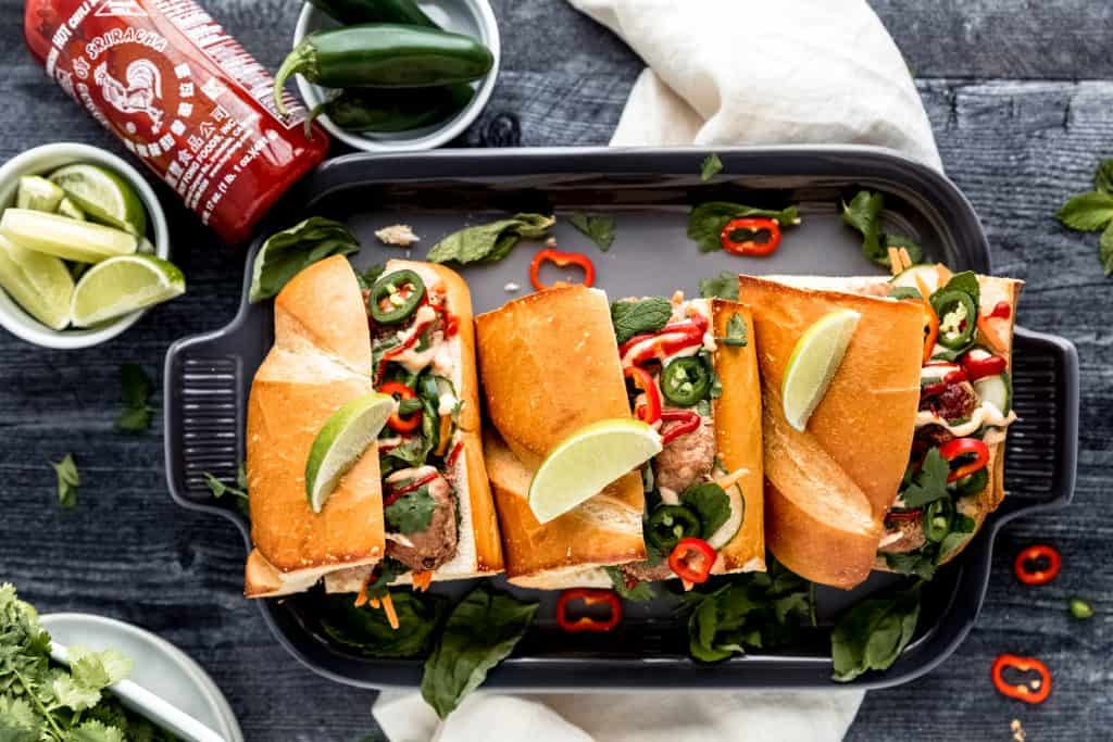tray of meatball banh mi with various green herbs, limes, a bottle or sriracha and a white linen on a dark weathered wood surface