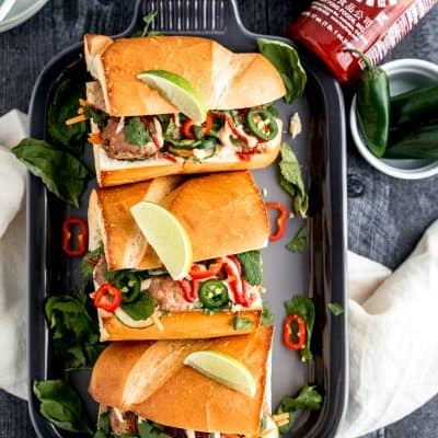 turkey meatball banh mi sandwiches on a grey platter on top of a dark weathered wood surface with a bottle of sriracha and various green toppings such as limes, mint, basil, cilantro and fresh jalapeno