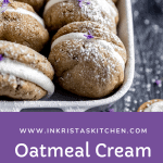 oatmeal cream pies lined up in a white baking dish sprinkled with powdered sugar and lavender on top of a dark wood surface that has powdered sugar dust on it