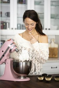 krista in a white sweater with a pink kitchen aid mixer eating cool whip off of one finger