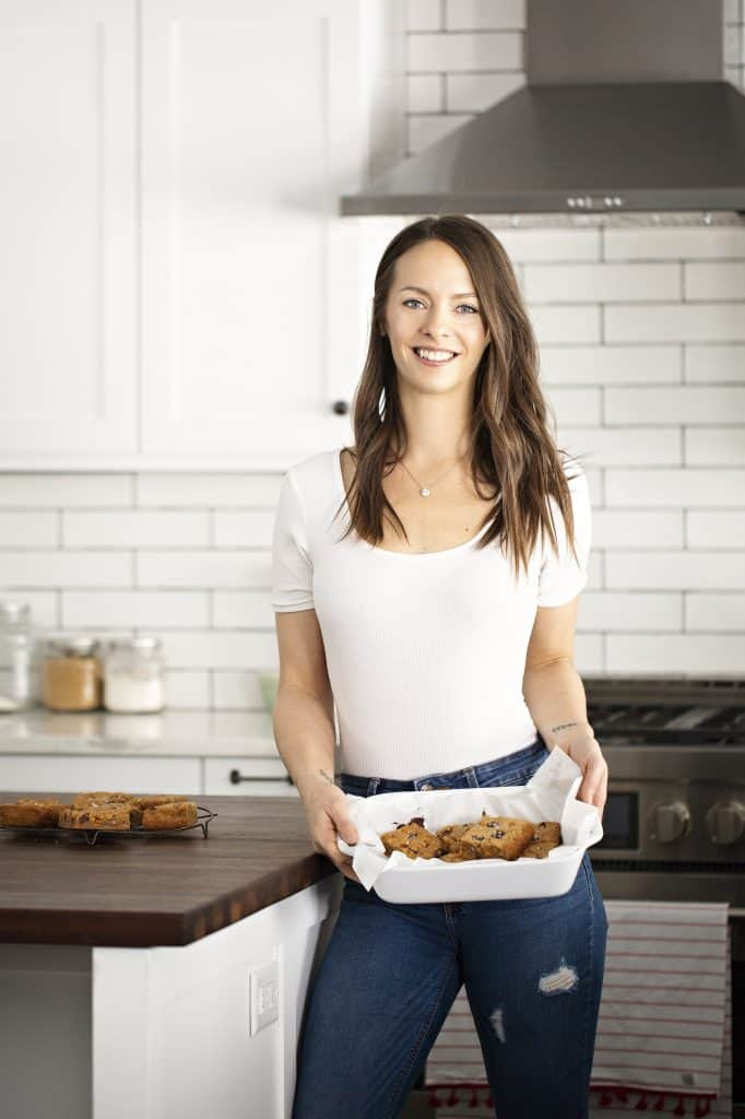krista standing in a white kitchen with a white shirt on holding a white pan of blondies facing the camera smiling