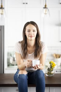 krista sitting on a counter in a white kitchen with a cup of coffee in a white mug and yellow flowers in a vase to the side of her