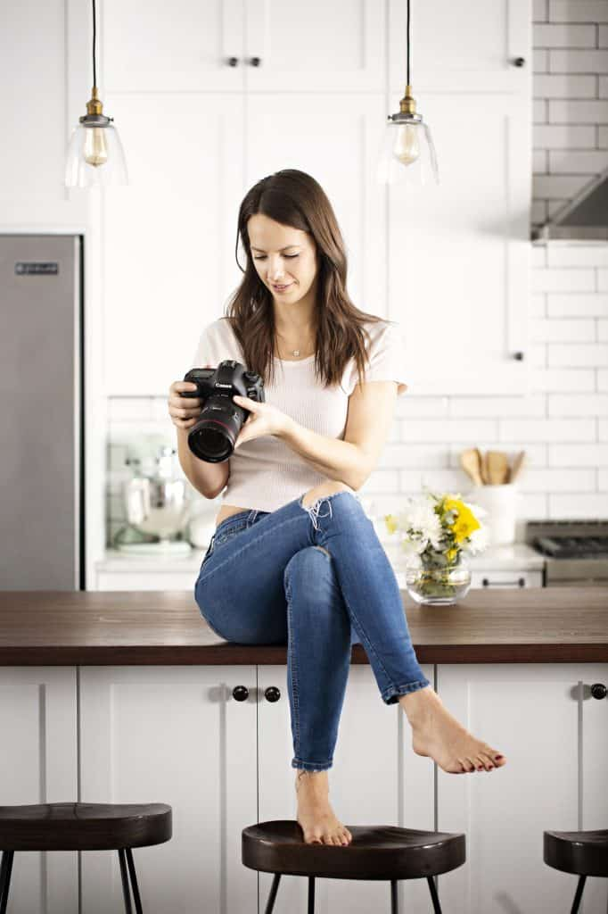 meet Krista sitting on the kitchen island with legs crossed viewing photos of delicious food on her camera