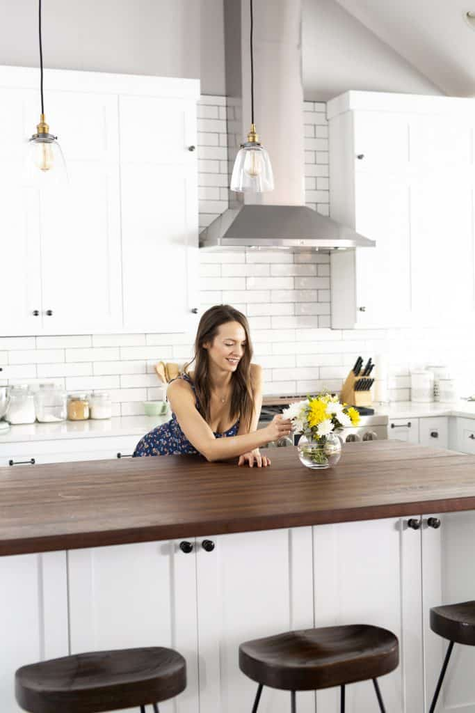 krista leaning over a counter in a blue dress in a white kitchen touching flowers in a vase