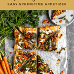 asparagus tart cut into triangles with one missing. topped with carrots and fresh herbs
