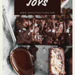 overhead shot of pecan joy candy bars with flaky sea salt and a spoon of melted chocolate. one of the candy bars is split in half to see the coconut on the inside