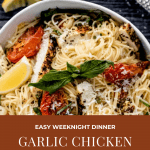 garlic chicken pasta in a bowl with fresh basil, roasted tomatoes and a lemon wedge