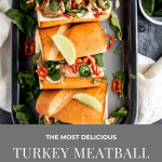 turkey meatball banh mi on a dark grey tray with limes and jalapenos