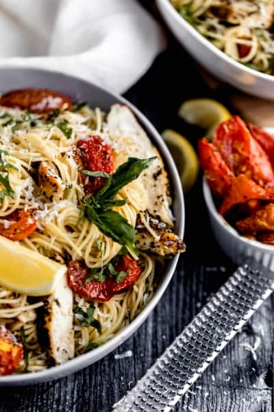 a bowl of garlic chicken pasta with a lemon wedge, grated asiago cheese, fresh basil and roasted tomatoes in it. A microplane grater off to the side with a bowl of roasted tomatoes and squeezed lemon wedges