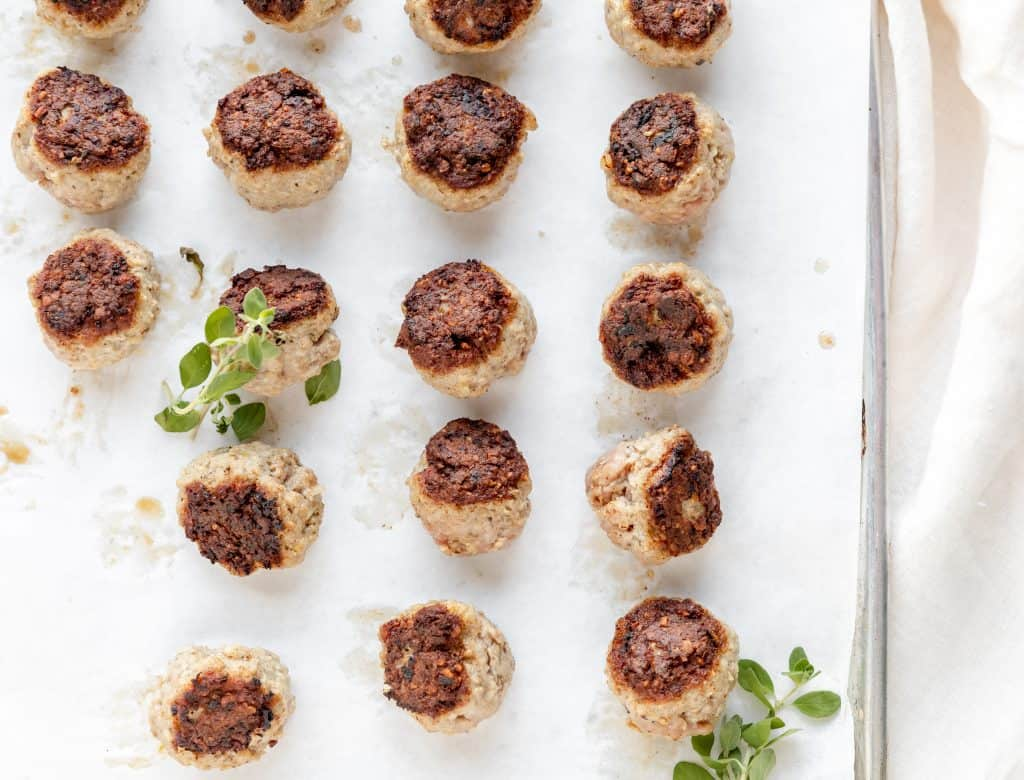 seared meatballs on a parchment paper lined baking sheet with a little fresh oregano on them