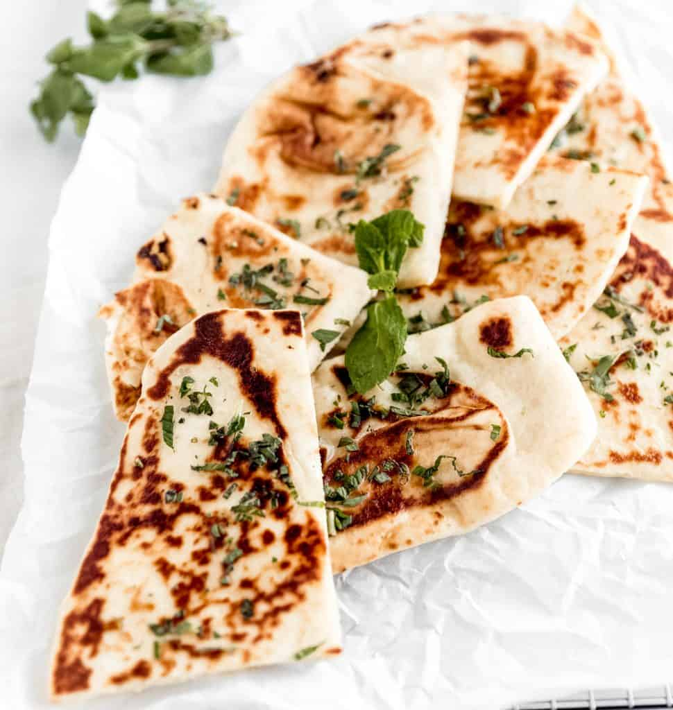 naan cut up into quarters on a sheet of parchment paper topped with fresh mint and oregano