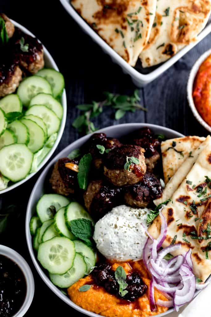 2 mediterranean bowls with meatballs, cucumbers, garlic cheese spread, naan, red onion, chutney and mint leaves in a grey and white bow with a bowl of cherry pepper hummus on the side on a dark surface