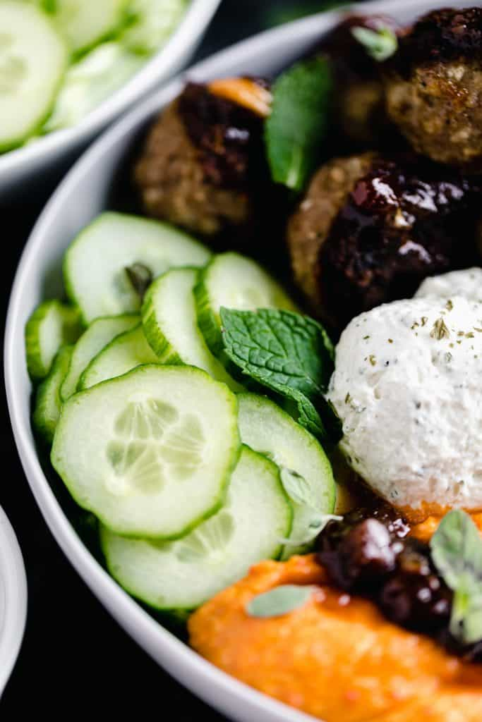 close up of the Mediterranean Bowl with all of the cucumber, garlic cheese spread, meatballs, lemon chutney, cherry pepper hummus and fresh mint and oregano