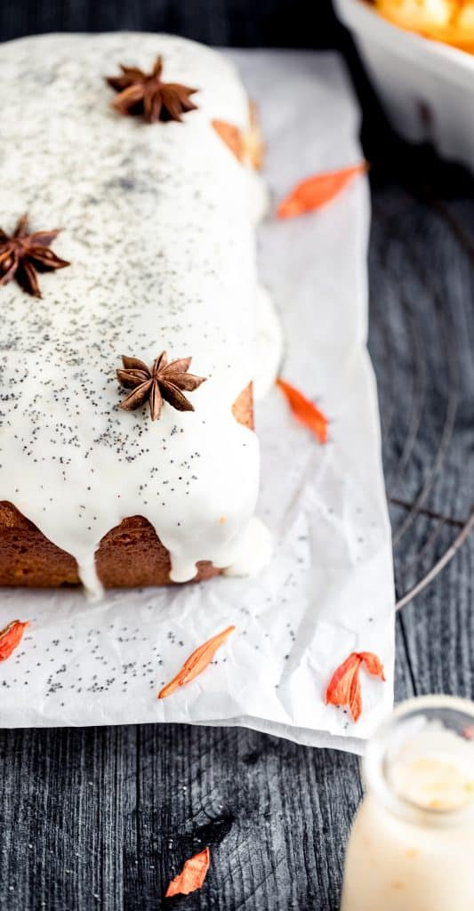 a whole loaf of orange poppy seed bread with yogurt glaze sitting on top of white parchment paper topped with whole star anise and poppy seed. orange dried flowers scattered on the parchment paper