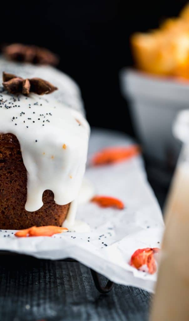 Straight on view of orang poppy seed bread with the yogurt drip coming down the side. topped with whole star anise and poppy seeds. dried orange flowers sitting on top of parchment paper