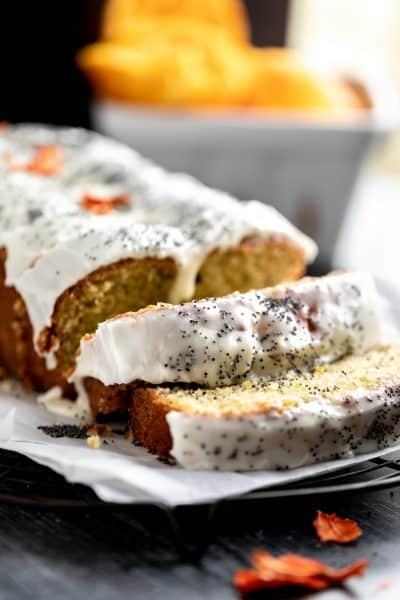 Orange Poppy Seed Bread with an orange yogurt glaze sitting on top of parchment paper on a cooling rack. 2 slices and the rest of the loaf is whole. topped with poppy seeds and dried orange flowers