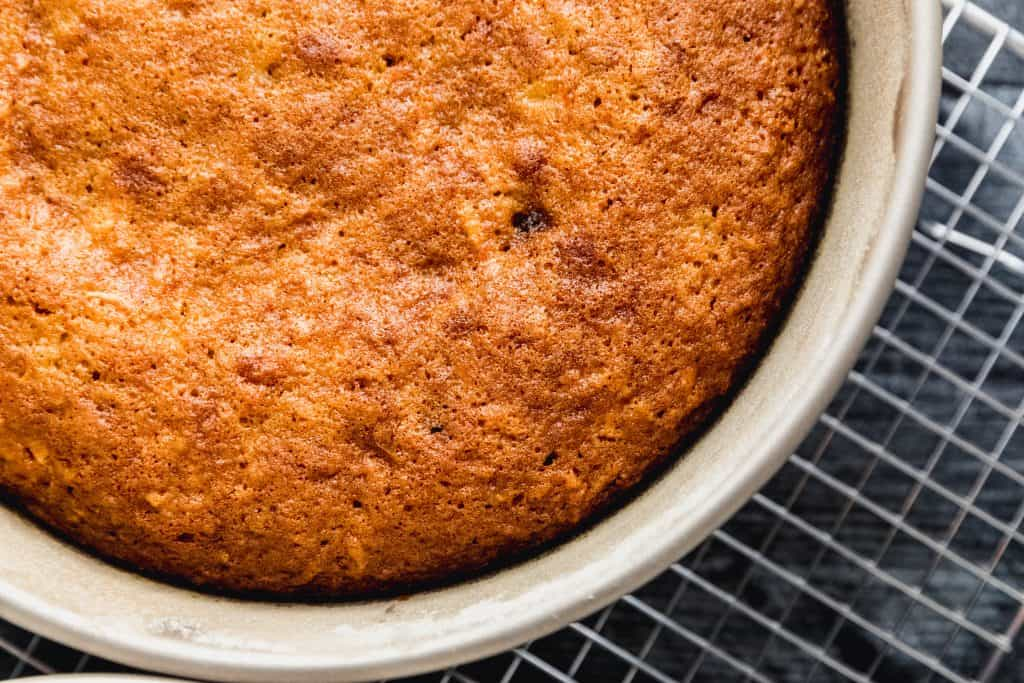 baked carrot cake still in the pie pan on top of a cooling rack on a dark surface