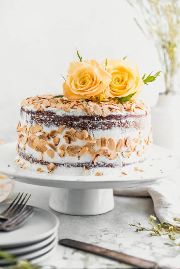 almond carrot cake on a stand covered with toasted almonds and yellow roses on top. grey plates in the bottom left corner with antique silverware on them and a vase with greens in the back right corner