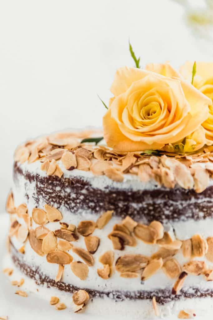 close up of almond carrot cake with toasted almonds on the outside and yellow roses sitting on top of the cake