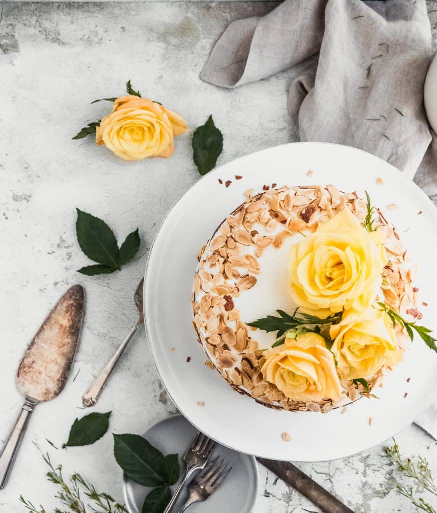 top view of almond carrot cake with toasted almonds and yellow roses on top surrounded by a linen, cake spatula and roses with leaves