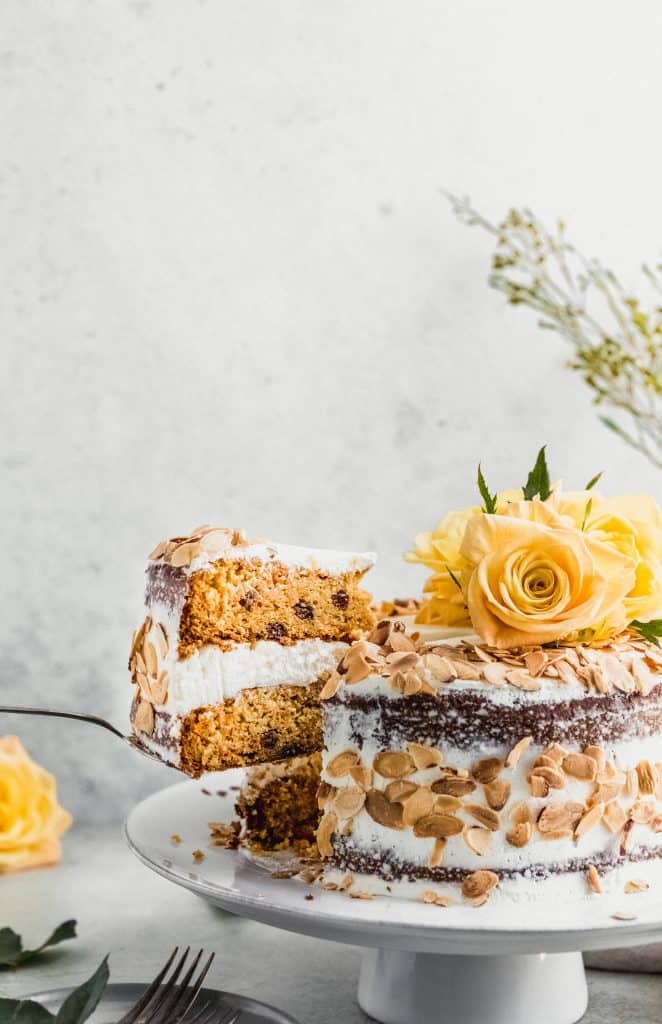 almond carrot cake on a stand with one slice cut and a cake server lifting it up away from the cake