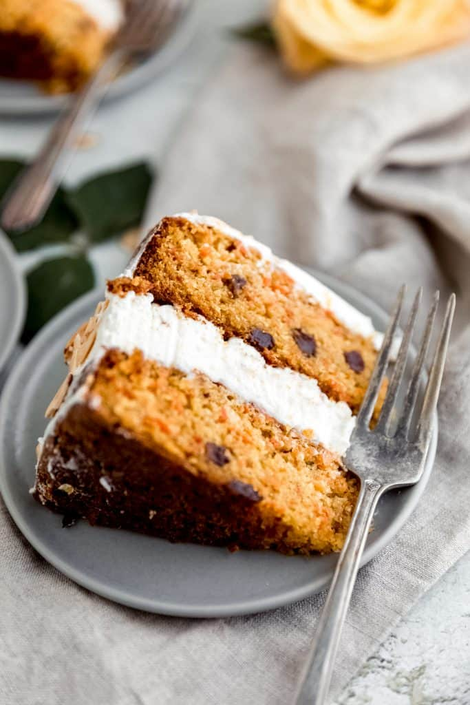 one slice of almond carrot cake sitting on a grey plate with a fork next to it sitting on a surface with a linen