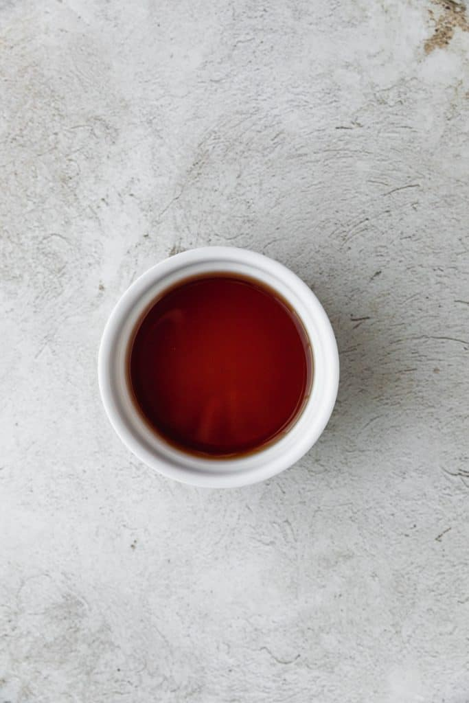 a ramekin filled with sherry vinegar on a light surface