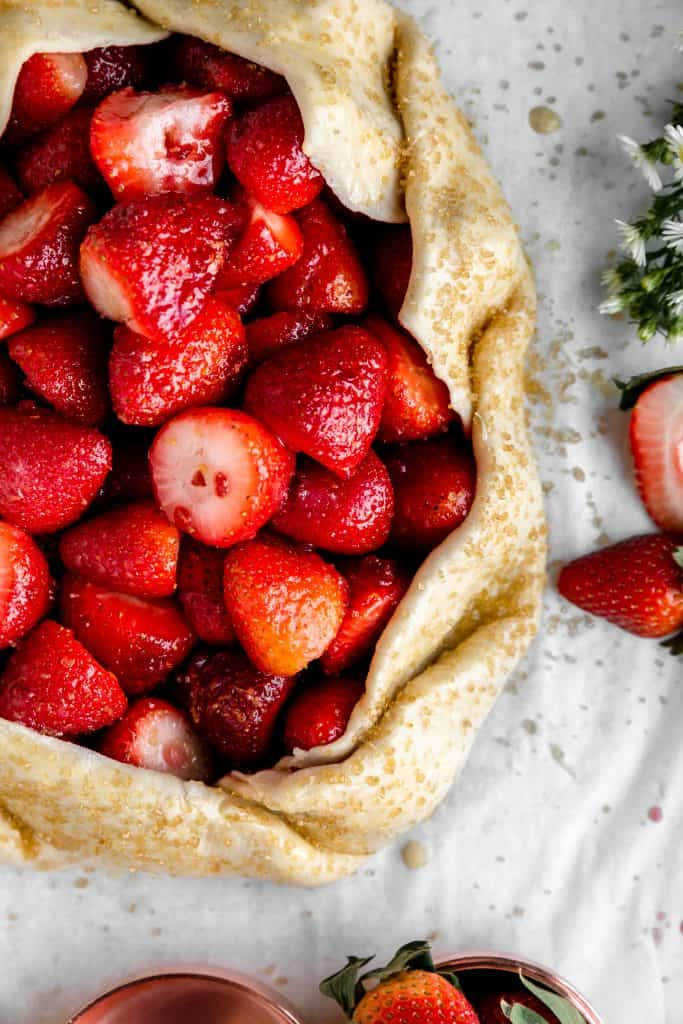 overhead shot of raw strawberry galette right before it goes into the oven with sugar sprinkled on the crust