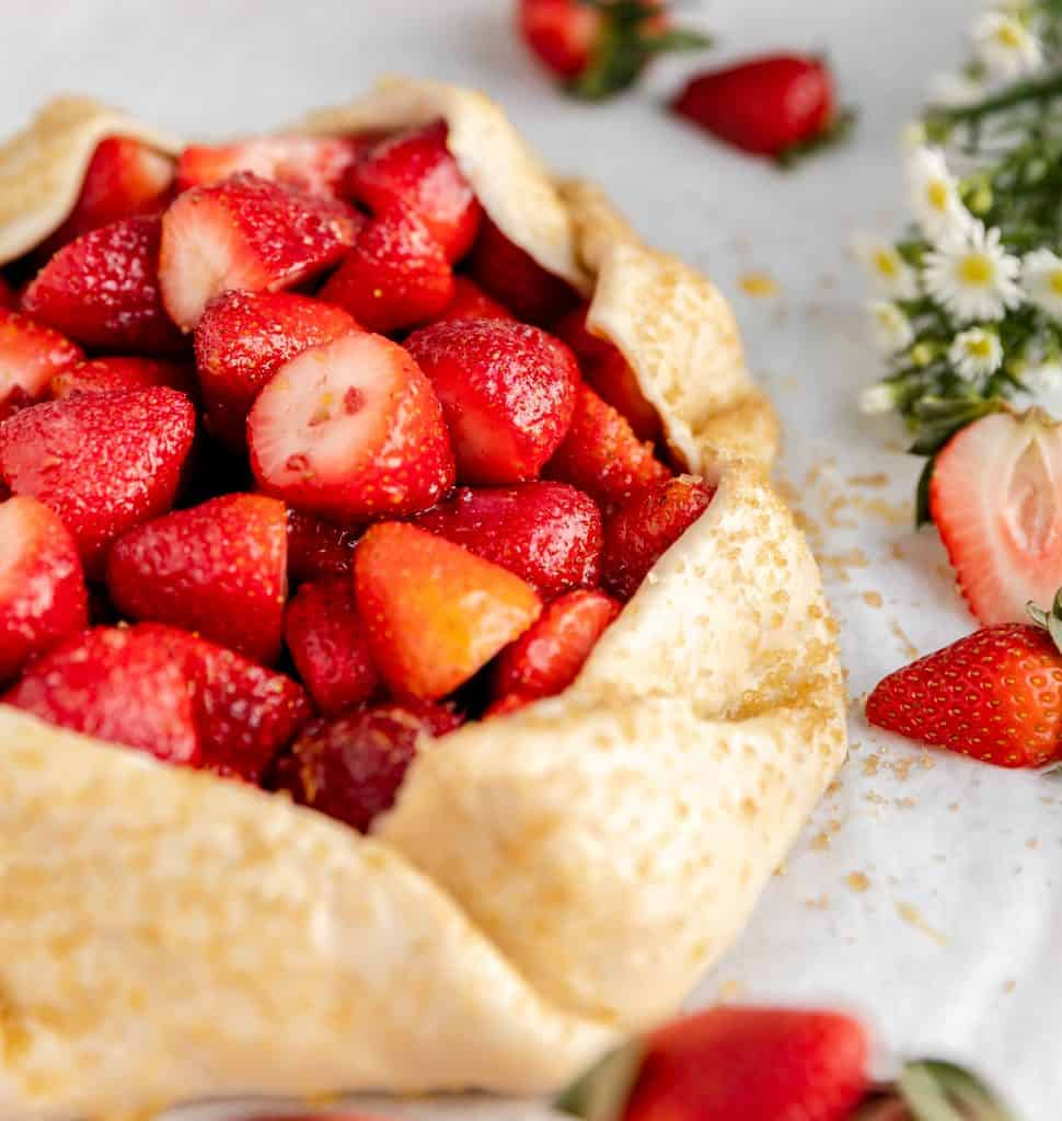 the galette still raw with a close up of the dough and filling before it goes in the oven. flowers and strawberries to the side of the galette